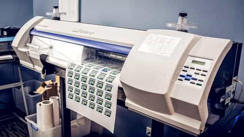 A Digital Heater Printer printing out logo designs for digital heat transfer
