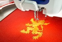 Embroidery machine and finish embroider gold lion design on red cotton fabric shirt, close up picture, copy space on the left side.