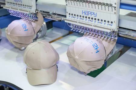 The emboirdery machines putting logos stiched into hats